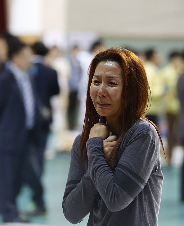 The mother of a passenger who was on a sinking ferry reacts as she finds her son at a gym where rescued passengers gather in Jindo