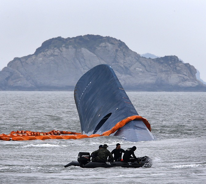 A vessel involved in salvage operations passes near the upturned South Korean ferry Sewol in the sea off Jindo April 17