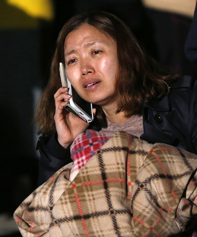 A family member of a missing passenger who was on the South Korean ferry Sewol which sank in the sea off Jindo cries as she waits for a rescue team's arrival at a port where family members of missing passengers gathered in Jindo