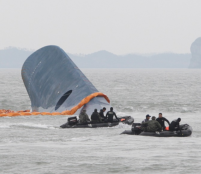 Members of the South Korean Navy search for missing passengers at the site of the sunken ferry off the coast of Jindo Island