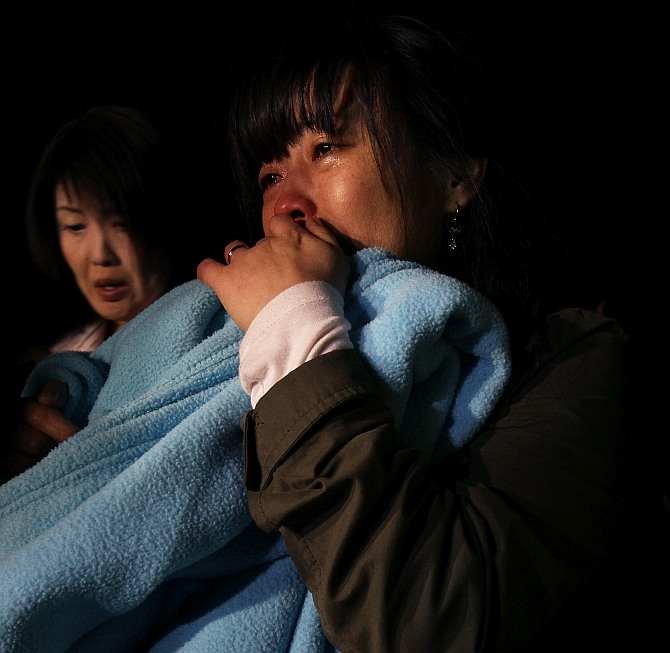 A relative weeps as she waits for missing passengers of a sunken ferry at Jindo port
