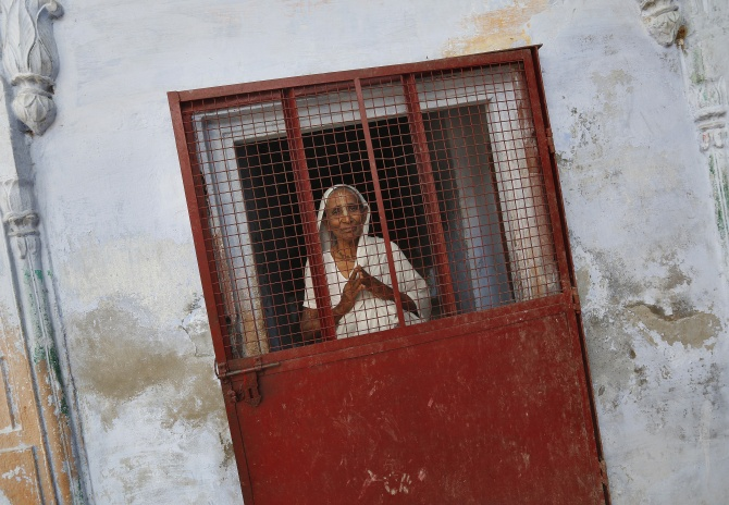 A widow poses at the entrance of a staircase at the Meera Sahavagini ashram in Vrindavan in Uttar Pradesh.