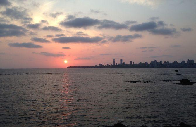 The sky turns a pinkish hue as the sun sets over Mumbai's Marine Drive.