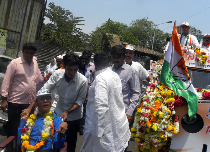 A handicapped constituent is garlanded by Milind Deora in Mazgaon.