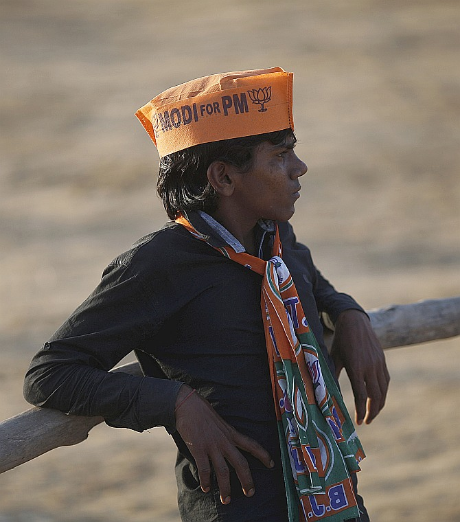 A supporter of Narendra Modi waits to leave after a rally in Gurgaon on the outskirts of New Delhi