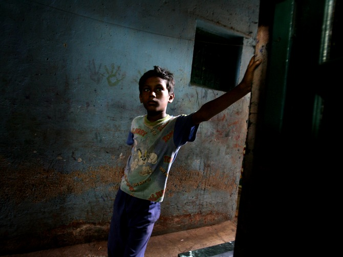 In search of hope: A young boy looks on in an alley at the Dharavi slums in Mumbai.