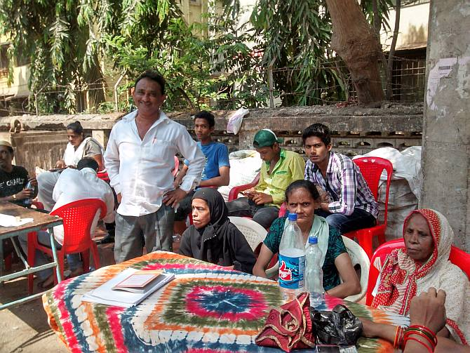 Anwar Shaikh (in white shirt, standing), a Shiv Sena upashakhapramukh stands beside his polling booth agents outside Behrampada. Seated behind him on the red chair is Irfan Syed, a Congress-appointed polling booth agent with his team members