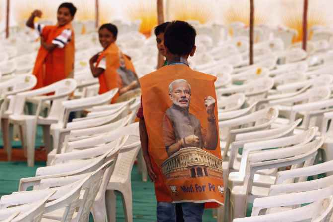 Children wear vests with images of Modi during an election campaign rally in Surendranagar