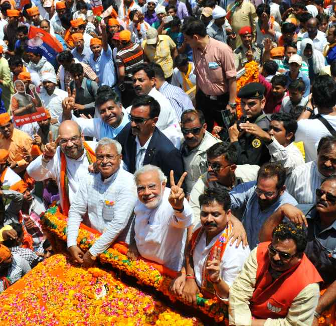 Modi flashes the victory sign as he heads to file his nomination in Varanasi on Thursday