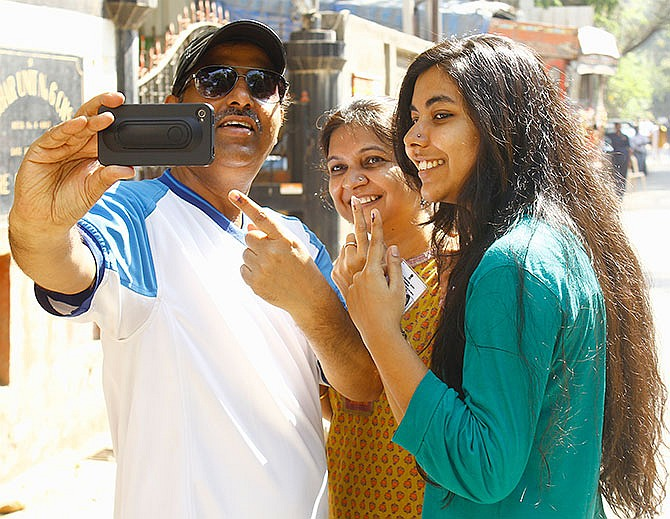 A family poses for a selfie after casting vote in Lokhandwala locality in Andheri, Mumbai