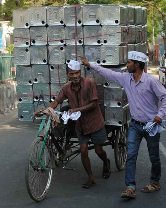 An AAP volunteer places a party cap on a member of the public in Lucknow.