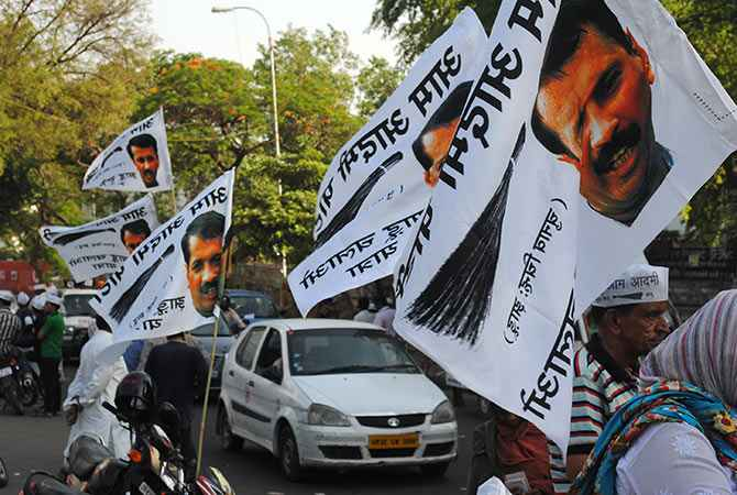 Posters and flags showing AAP chief Arvind Kejriwal at a road show in Lucknow.