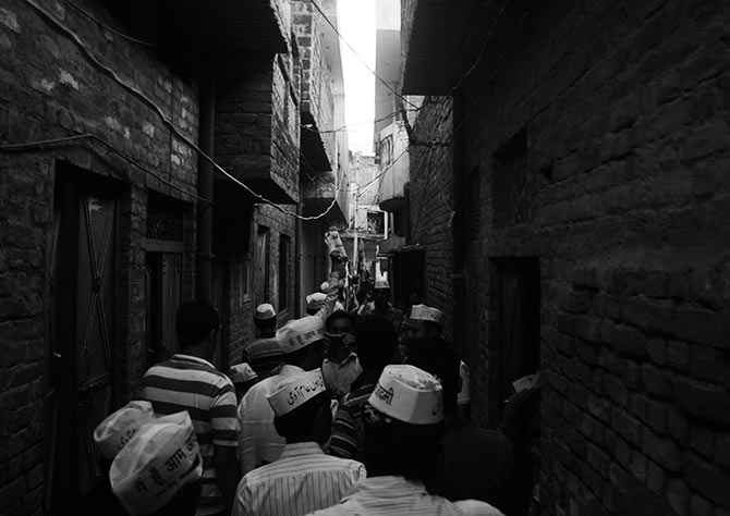 AAP volunteers pass through a narrow bylane in Lucknow.