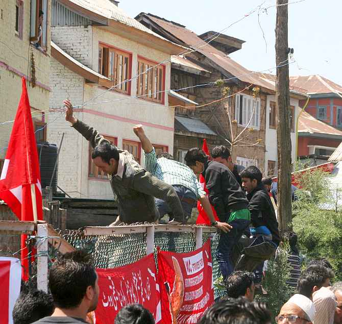 National Conference supporters jump a wall to safeguard themselves following an explosion near a rally venue in Srinagar on Sunday