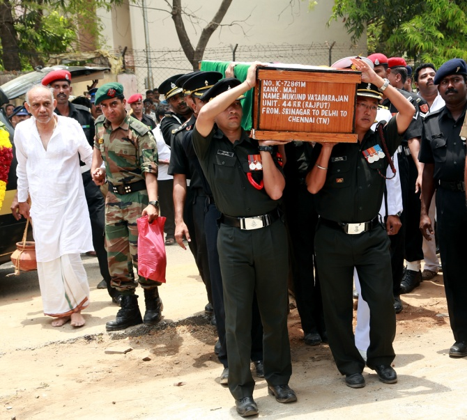 The coffin being carried inside the crematorium accompanied by the major's father father R Vardarajan (in white)
