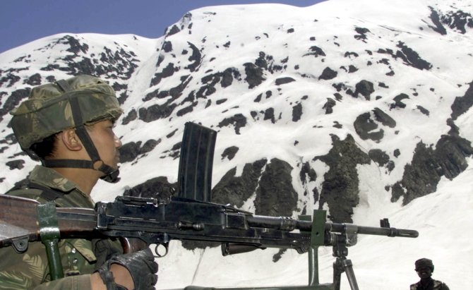 A soldier stands guard at a snow-capped mountain near Srinagar.