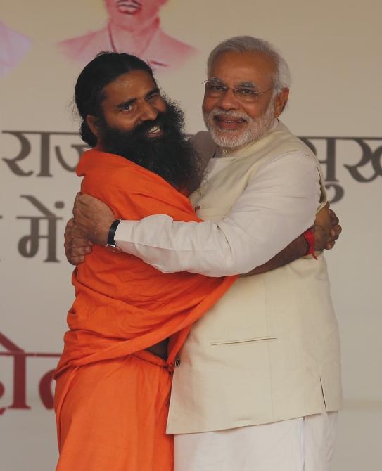 Narendra Modi hugs Ramdev, who recently made anti-Dalit remarks, during a yoga 'mahotsav' in New Delhi.