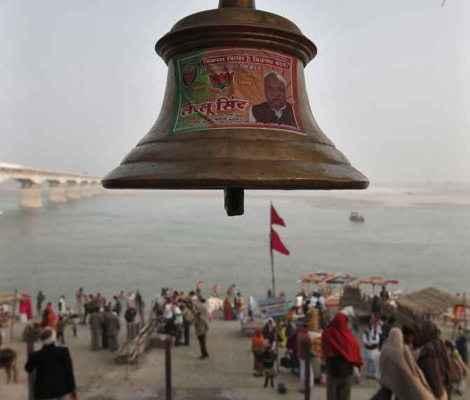 A temple bell pasted with a pamphlet of the BJP candidate is seen on the banks of the Sarayu in Ayodhya.