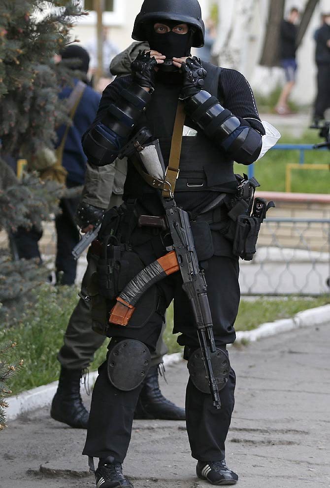 A pro-Russian armed man stands guard near the local police headquarters in Luhansk, eastern Ukraine.