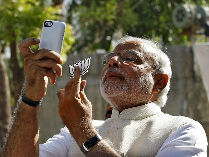 Modi takes a selfie on his phone after he casts his vote in Ahmedabad