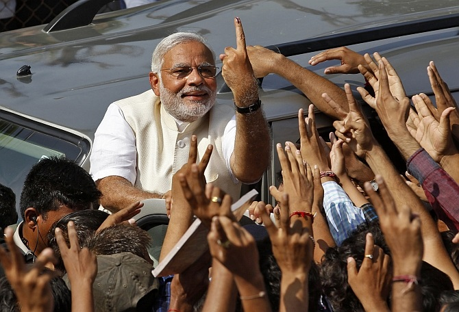 Modi shows his ink-marked finger to his supporters in Ahmedabad