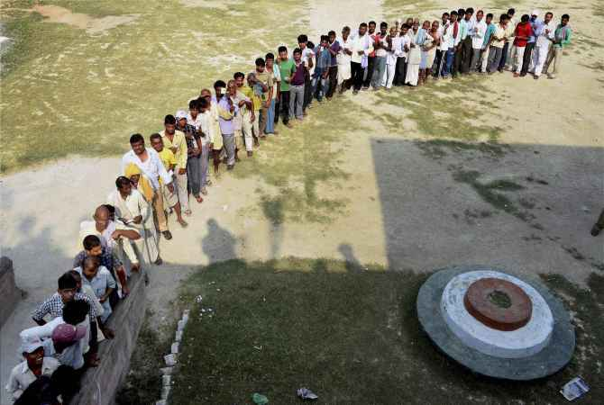 Voters line up to cast their ballot at a polling booth in Bihar's Samastipr district