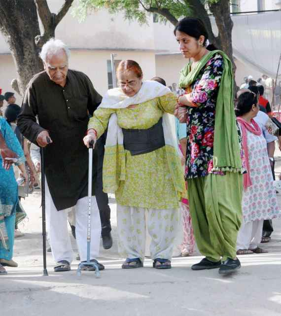 An elderly woman arrives at a polling booth in Lucknow on Wednesday