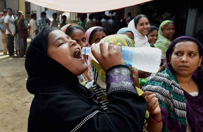 A woman quenches her thirst at a polling station in Howrah district, West Bengal on Wednesday