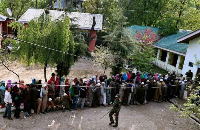 People wait to cast their vote for Srinagar Lok Sabha constituency at a polling station in Ganderbal district on  Wednesday.