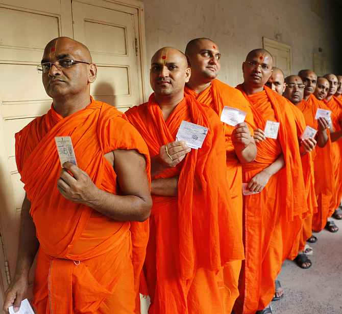 Monks of Swaminarayan temple queue up to cast their votes at a polling booth in Ahmedabad on Wednesday