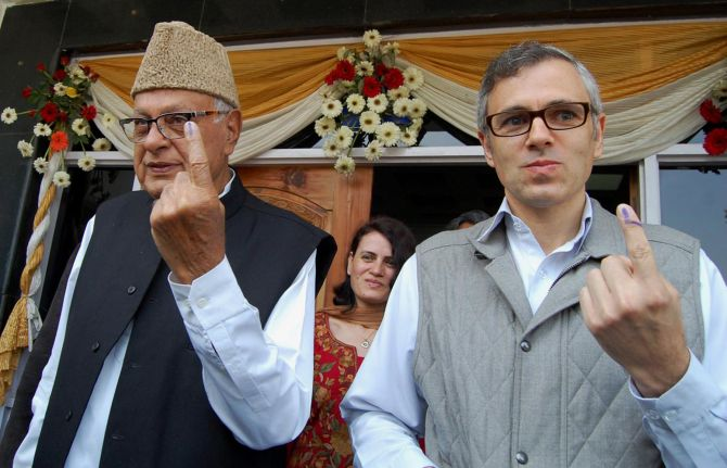 Chief Minister Omar Abdullah with New and Renewable Energy minister Dr Farooq Abdullah show their inked finger after casting their vote