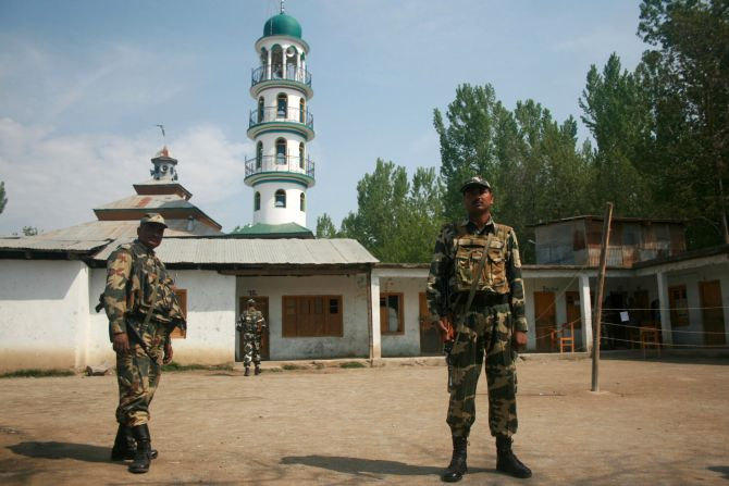 Security personnel stand guard outside an empty polling booth in Srinagar