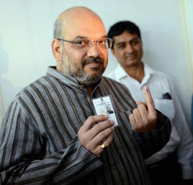 BJP leader Amit Shah shows his inked finger after casting his vote for Lok Sabha polls at a polling station in Ahmedabad.