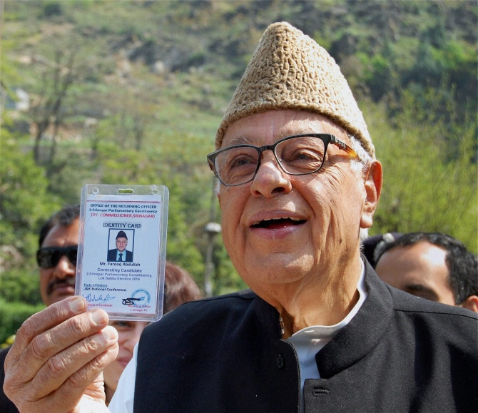 Union Minister and National Conference candidate Farooq Abdullah shows his voter identity card before casting his vote for Lok Sabha elections at a polling station in Srinagar.