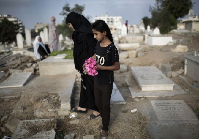 A Palestinian woman and girl carry flowers to a family grave at a cemetery in Gaza City.