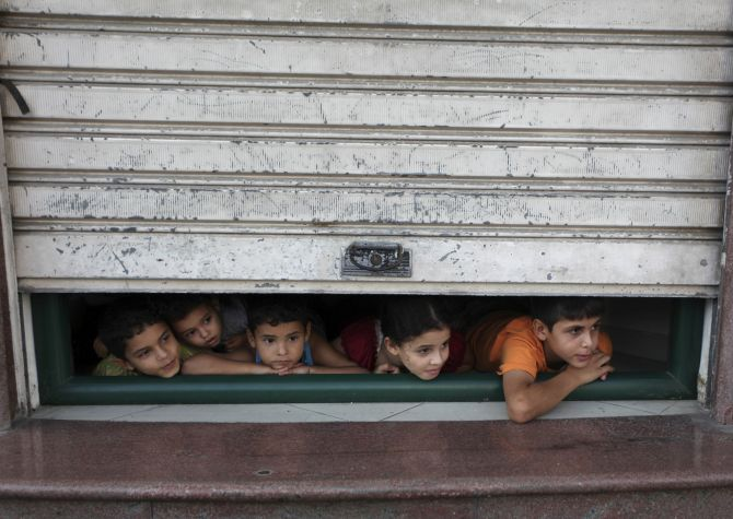 Palestinian children look through a store shutter at ambulances transporting casualties during Israeli offensive in Gaza City.