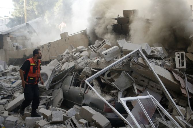 A Palestinian firefighter participates in efforts to put out a fire from the wreckage of a house, which witnesses said was destroyed in an Israeli air strike, in Gaza City.