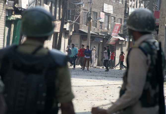 Protestors pelt stones at security personnel during clashes in Srinagar on Friday