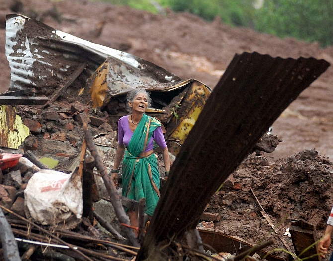 A villager search for family members among the debris of her house at the site of a landslide in Malin village, in Maharashtra on Wednesday