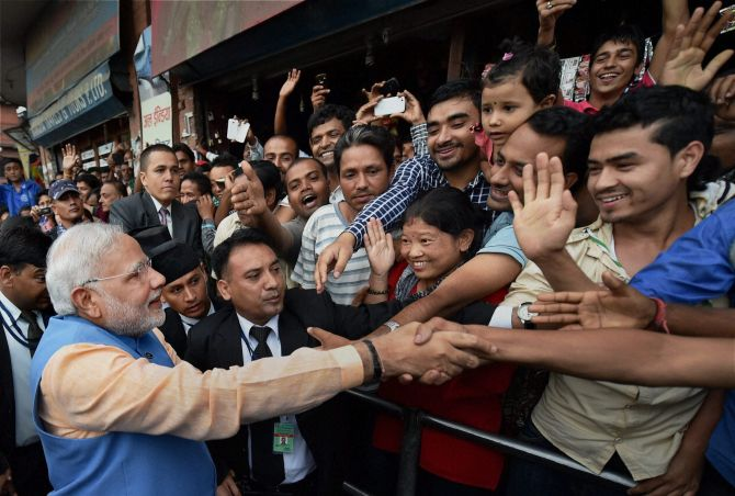 Prime Minister Narendra Modi greets people on the streets on his way back to the hotel after addressing the Nepalese Parliament in Kathmandu
