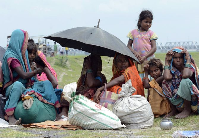 Villagers with their belongings sit in a relief camp after their evacuation at Supaul, Bihar.