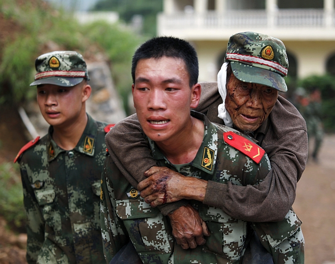 A paramilitary policeman carries an elderly man on his back after an earthquake hit Ludian county of Zhaotong, Yunnan province