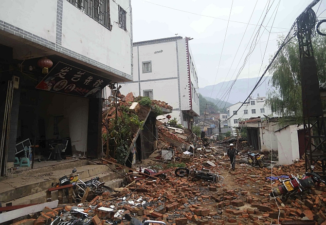 Debris of collapsed houses are seen scattered along a street, after a deadly earthquake hit Longtoushan town
