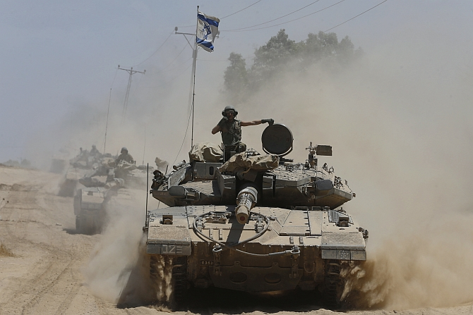 An Israeli soldier rides atop a tank near the border with the Gaza Strip