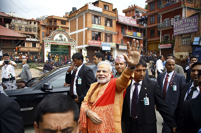 Modi waves at supporters waiting to greet him at the premises of Pashupatinath Temple
