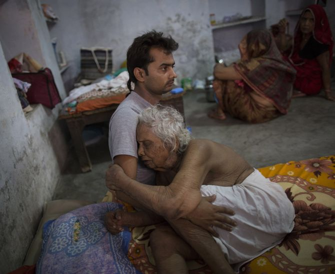 Bhogla Devi, 97, is comforted by her grandson Divyesh Tiwari as she cries in pain at Mukti Bhawan.