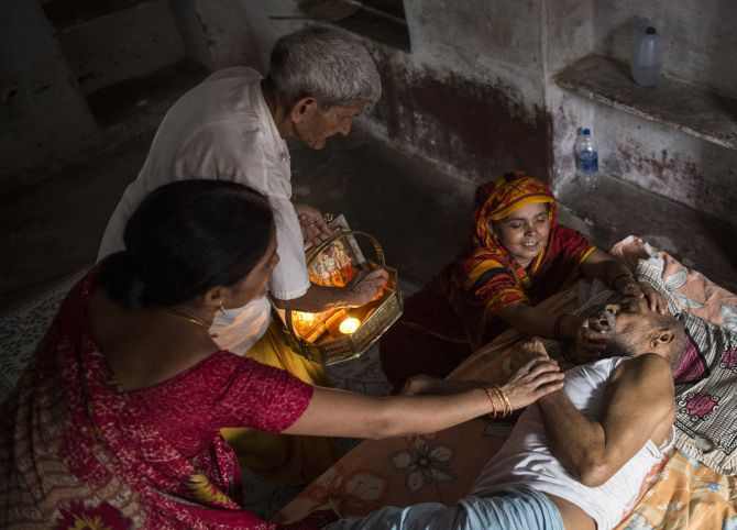 Kishore Pandey, 82, lies on a bed as his daughter, Usha Tiwari, holds him and a priest stands by them.