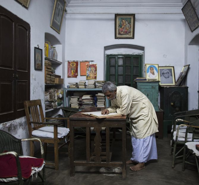 Bhairav Nath Shukla, manager of Mukti Bhavan looks through the records inside his office in Varanasi.
