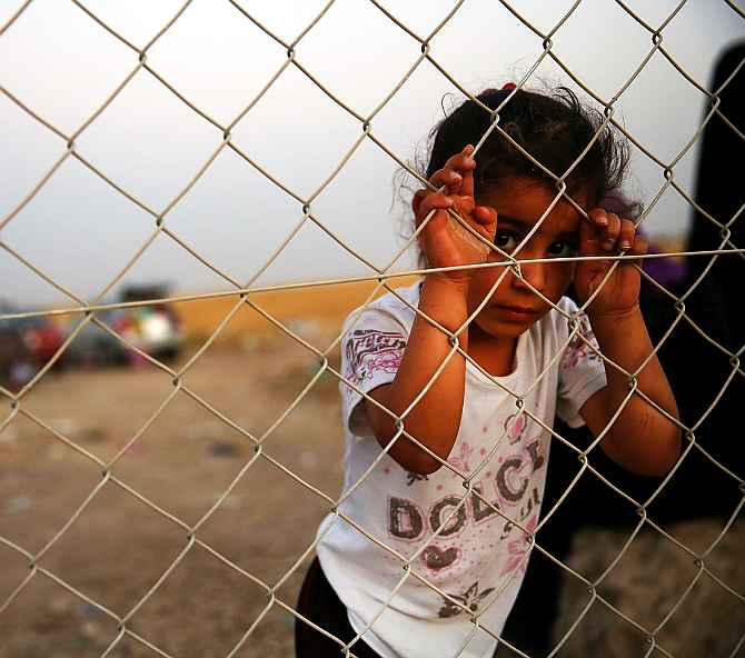 A child waits with her family outside a temporary displacement camp for Iraqis caught up in the fighting against ISIS in and around Mosul. (Inset) Dr Bonny Ibhawoh