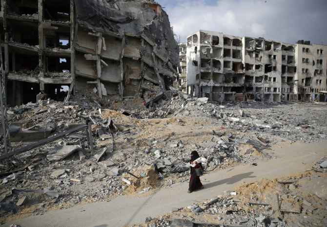 A Palestinian woman walks past buildings destroyed by Israeli air strikes and shelling at Beit Lahiya, Gaza Strip.